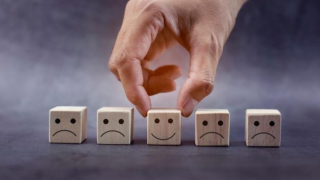 Mani del primo piano che tengono l'icona della faccina sorridente sul concetto di leadership di valutazione del servizio di cubo di legno