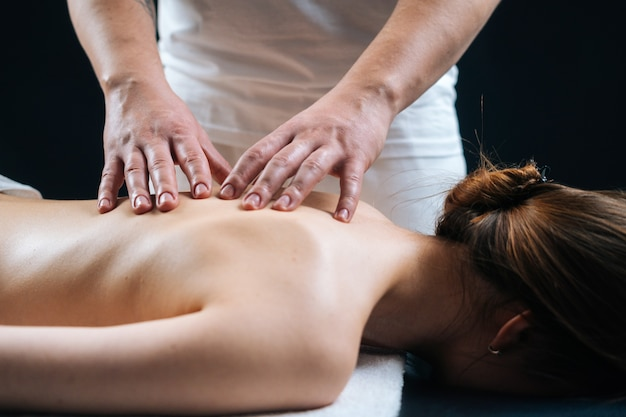 Mani del primo piano del massaggiatore maschio che fa massaggio alla schiena alla giovane donna rilassata nel salone della stazione termale