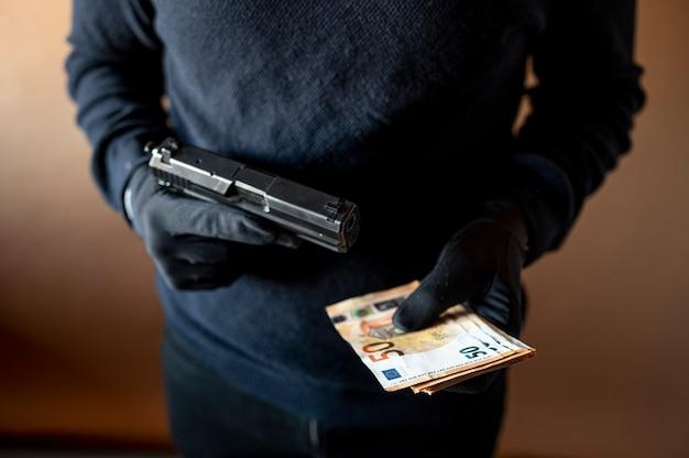 Primo piano delle mani di un ladro con una pistola e una manciata di banconote
