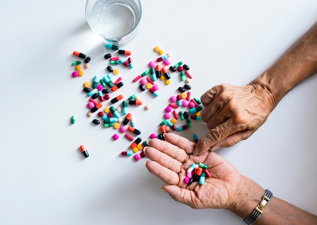 Primo piano delle mani che prendono il trattamento sanitario delle pillole isolato