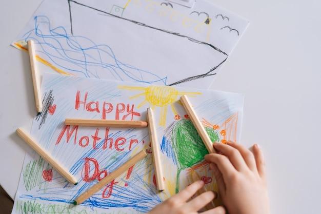 Primo piano delle mani di una ragazza irriconoscibile che disegna con matite colorate al tavolo