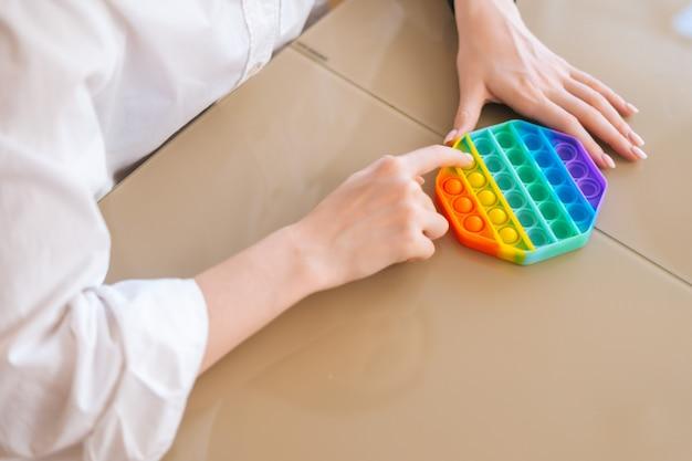 Primo piano le mani di una giovane donna irriconoscibile che gioca con il giocattolo fidget popit arcobaleno seduto al tavolo