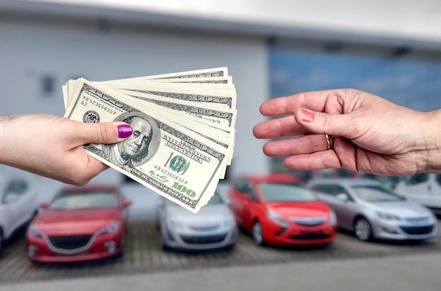 Primo piano sulle mani con il dollaro, affare con l'auto