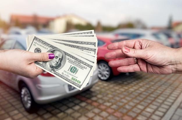 Primo piano sulle mani con il dollaro, affare con auto
