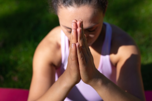 Primo piano delle mani della donna facendo esercizi di meditazione yoga all'aperto