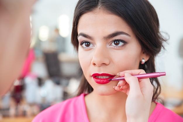 Primo piano delle mani di giovane visagiste femminile che applica rossetto rosso alle labbra di una donna attraente nel salone di bellezza