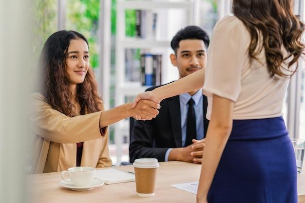 Stretta di mano del primo piano dopo l'accordo del colloquio tra la giovane donna asiatica e due manager
