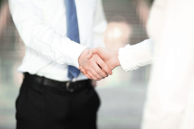 Primo piano. la stretta di mano di un uomo d'affari e di una donna d'affari. il concetto di partnership