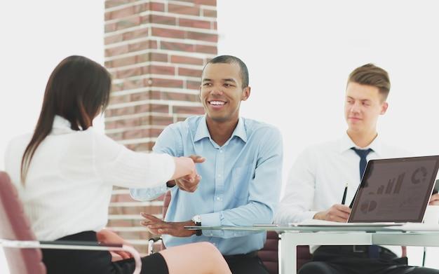 Primo piano.una stretta di mano di un manager e un dipendente in ufficio