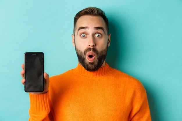 Primo piano di bel ragazzo barbuto in maglione arancione che mostra lo schermo dello smartphone e sorridente che mostra il ballo di fine anno...