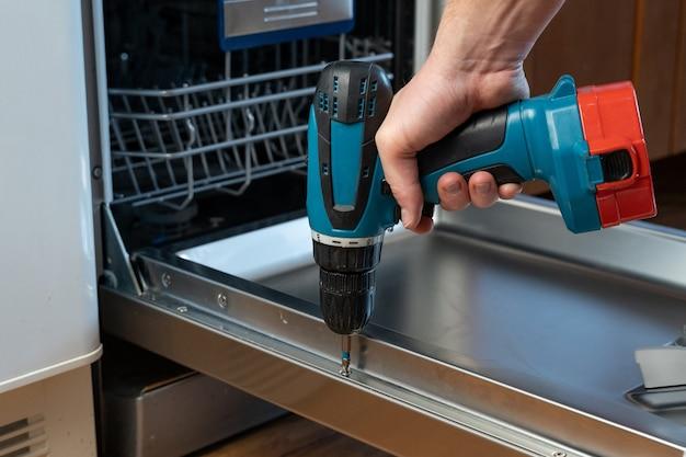 Primo piano di un tuttofare che ripara una lavastoviglie con un cacciavite elettrico