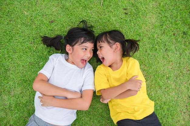 Primo piano di bambini asiatici felici sdraiati sull'erba verde green