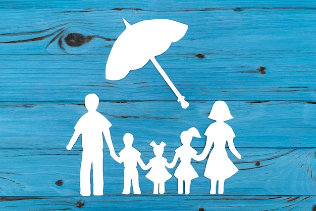 Primo piano della famiglia di carta felice sulla superficie del blu