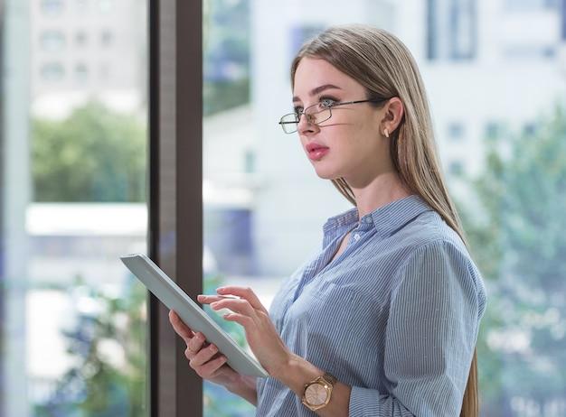 Primo piano di una donna felice con gli occhiali che utilizza un tablet pc in camera