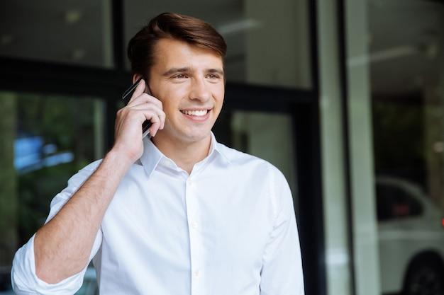 Primo piano di giovane uomo d'affari felice che comunica sul telefono cellulare vicino al centro di affari