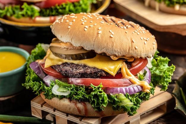 Primo piano di hamburger fatti in casa su fondo di legno. cibi assortiti da asporto o da consegnare.