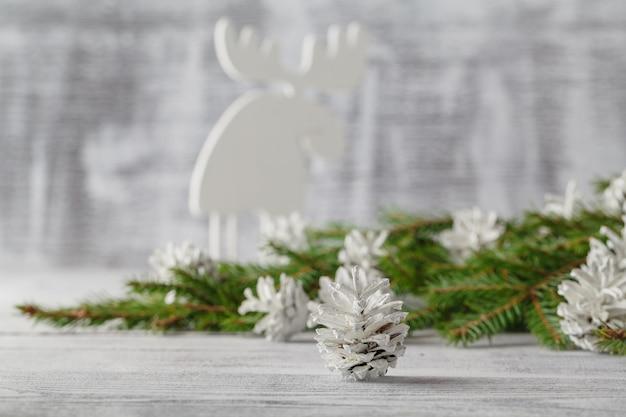 Vista orizzontale del primo piano di grande pigna, riposante nella neve bianca, con gli ornamenti di natale e il ramo di albero sempreverde
