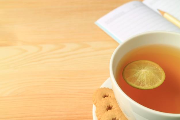 Tè caldo alla calce del primo piano con le carte per appunti allineate sfocate sulla tavola di legno con lo spazio della copia