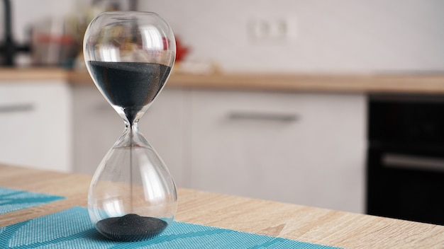 Primo piano della clessidra su un tavolo in legno bianco con cucina sfocata. concetto di tempo per cucinare.