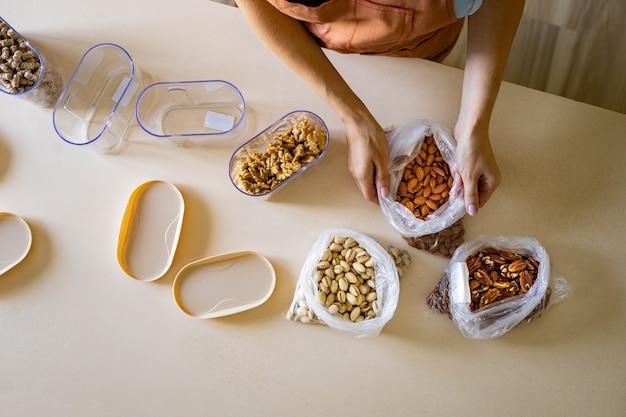 Mani della casalinga del primo piano che mettono il pacchetto di plastica dei dadi nella scatola del contenitore sul tavolo di legno in cucina