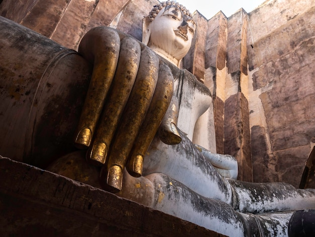 Primo piano enorme mano dell'antica statua del buddha all'interno della chiesa al wat sri chum temple, il famoso punto di riferimento nel parco storico di sukhothai, patrimonio mondiale dell'unesco in thailandia.