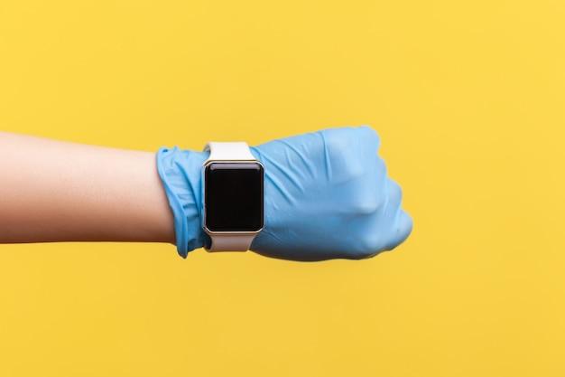 Primo piano della mano umana in guanti chirurgici blu che tengono e mostrano lo schermo dell'orologio intelligente.