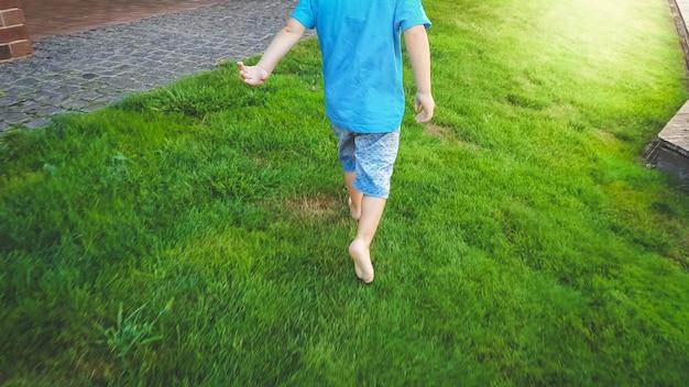 Immagine del primo piano di un bambino scalzo di 3 anni che corre sull'erba verde fresca al parco