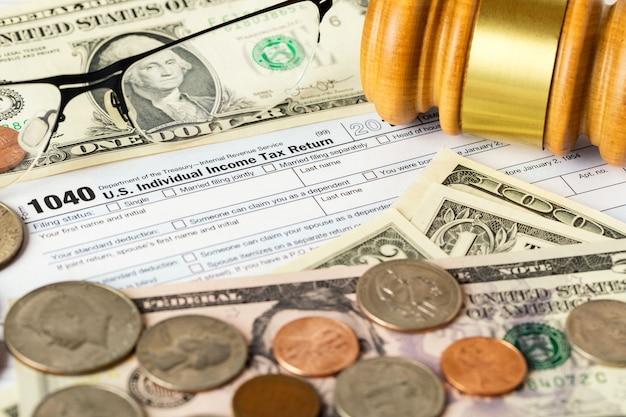 Immagine del primo piano del modulo di dichiarazione dei redditi individuale 1040 americano con denaro in dollari americani, monete, occhiali e martelletto del giudice.
