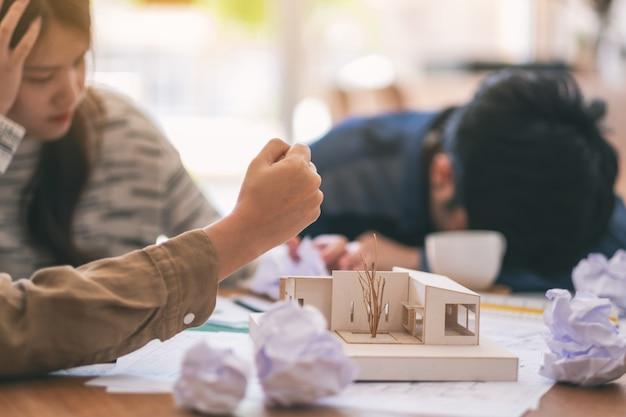 L'immagine del primo piano di un architetto arrabbiato e stressato cerca di distruggere a mano un modello di architettura sul tavolo quando fallisce al lavoro