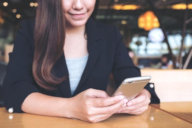 Immagine del primo piano di una donna di affari asiatica che tiene, usando e guardando smartphone