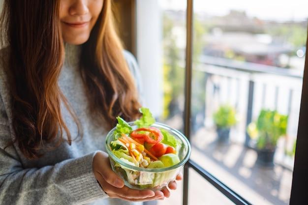 Immagine del primo piano di una donna asiatica che tiene in mano una ciotola di insalata di verdure miste fresche