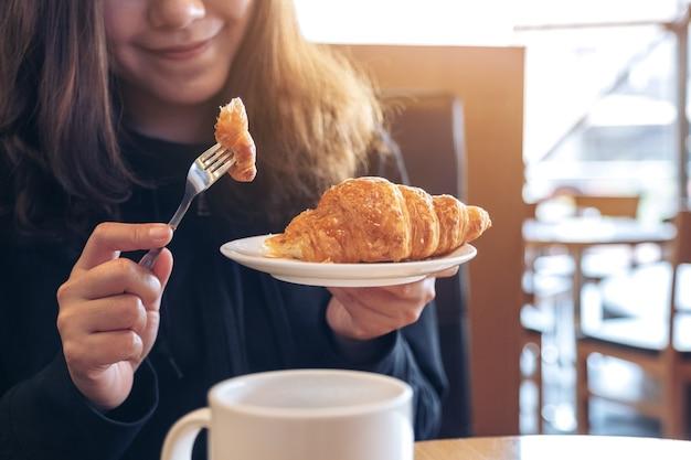 Immagine del primo piano di una donna asiatica che tiene e mangia un pezzo di croissant con una tazza di caffè sul tavolo