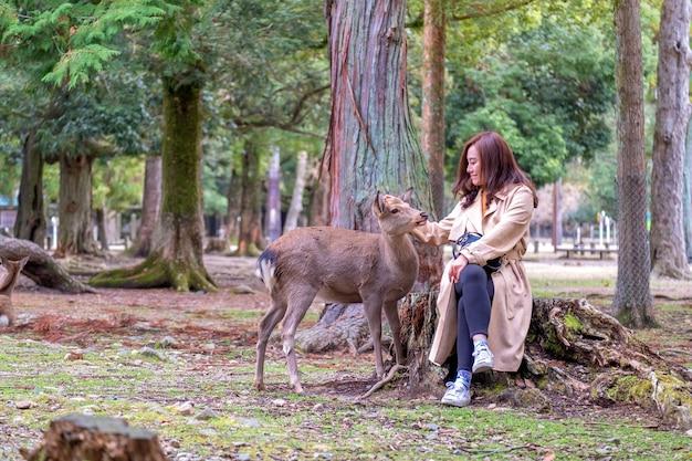 Immagine del primo piano di una donna asiatica che si siede e gioca con un cervo selvatico nel parco