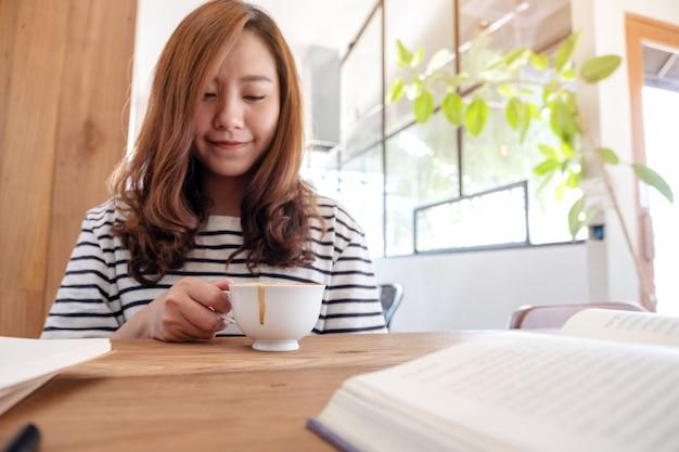 Immagine del primo piano di una bella donna asiatica che beve caffè mentre impara e legge libri