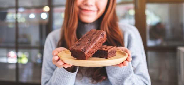 Immagine del primo piano di una bella donna asiatica che tiene una torta di brownie in un piatto di legno