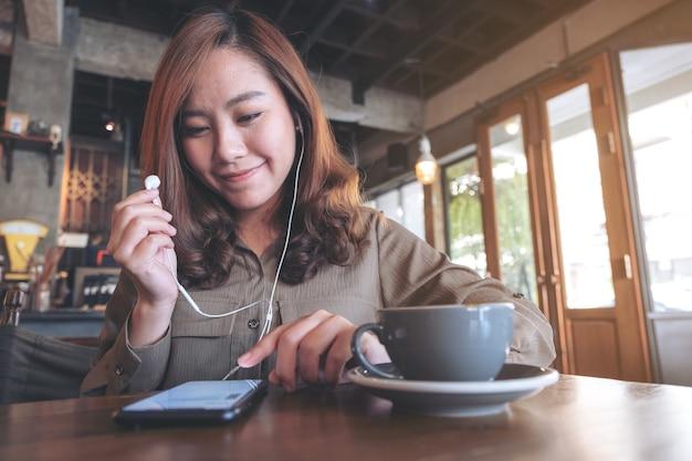 Immagine del primo piano di una bella donna asiatica che tiene gli auricolari mentre si ascolta la musica con il telefono cellulare nella caffetteria