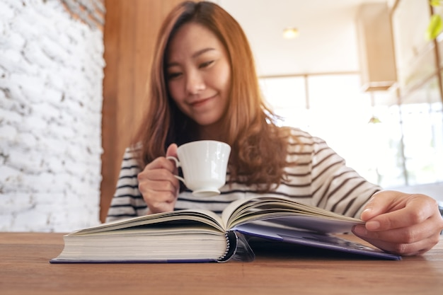 Immagine del primo piano di bella donna asiatica che tiene e legge un libro mentre beve il caffè