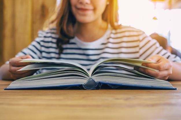 Immagine del primo piano di bella donna asiatica che tiene e che legge un libro