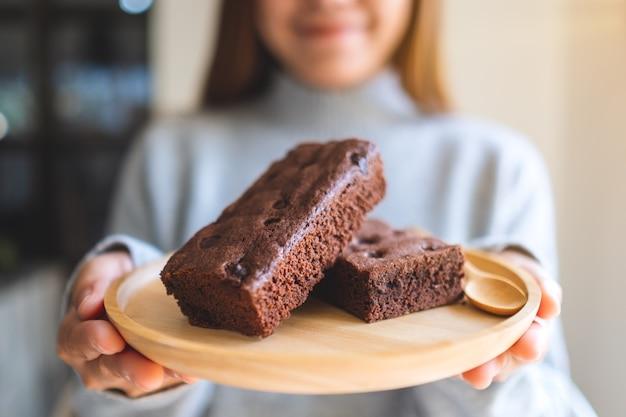 Immagine del primo piano di una bella donna asiatica che tiene e mostra una torta brownie in un piatto di legno