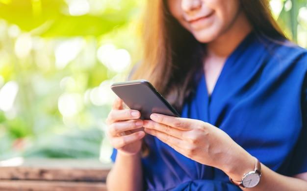 Immagine del primo piano di una bella donna asiatica che tiene, usa e guarda il cellulare in giardino