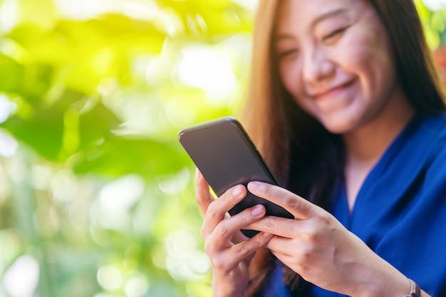 Immagine del primo piano di una bella donna asiatica che tiene, usa e guarda il telefono cellulare all'aperto