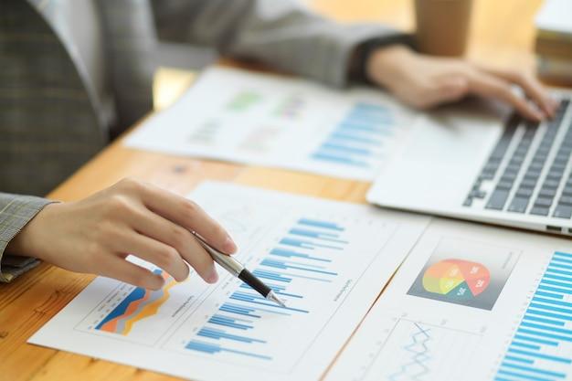 Immagine in primo piano di bellissime donne d'affari che lavorano in ufficio con un grafico dei rapporti sui dati finanziari e un laptop sulla scrivania