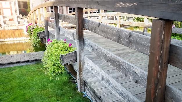 Immagine del primo piano di un bellissimo vecchio ponte di legno con fiori che crescono in vasi sul fiume calmo in una città europea