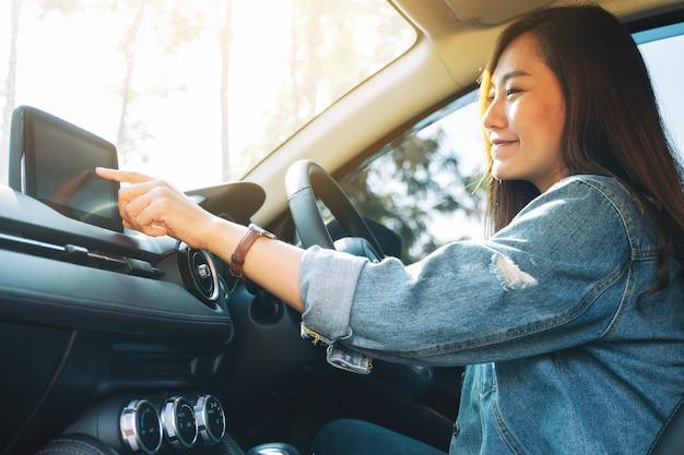 Immagine in primo piano di una bella donna che usa e punta il dito sullo schermo di navigazione mentre guida l'auto