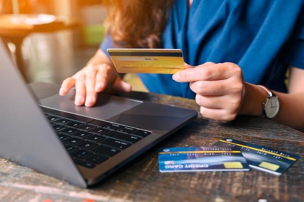 Immagine del primo piano di una donna d'affari in possesso di carte di credito mentre utilizza un computer portatile