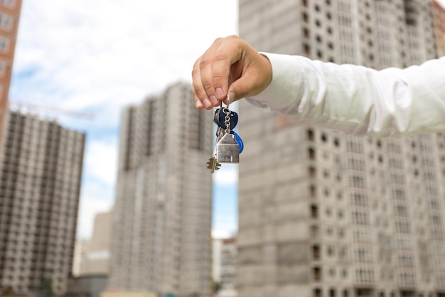 Immagine del primo piano dell'uomo d'affari che tiene le chiavi davanti al nuovo edificio