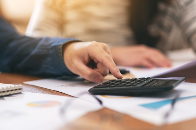 Immagine del primo piano di un uomo d'affari che usa la calcolatrice in una riunione d'affari