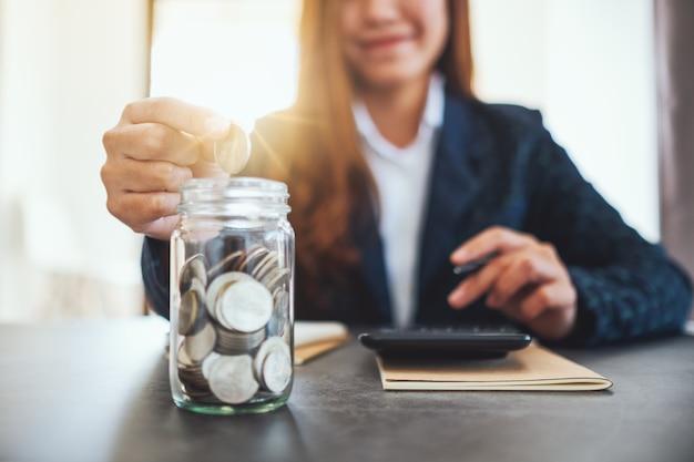 Immagine del primo piano di una donna d'affari che raccoglie e mette monete in un barattolo di vetro