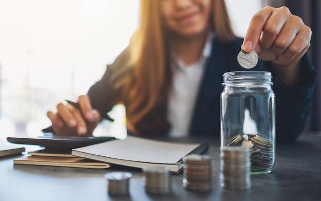 Immagine del primo piano di una donna d'affari che impila e mette monete in un barattolo di vetro
