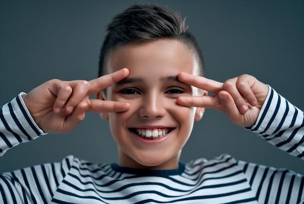 Immagine del primo piano di un giovane ragazzo caucasico positivo ottimista allegro che posa isolato sopra il fondo grigio della parete che mostra il gesto di pace.